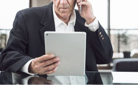 Man talking on mobile phone while looking at a tablet.